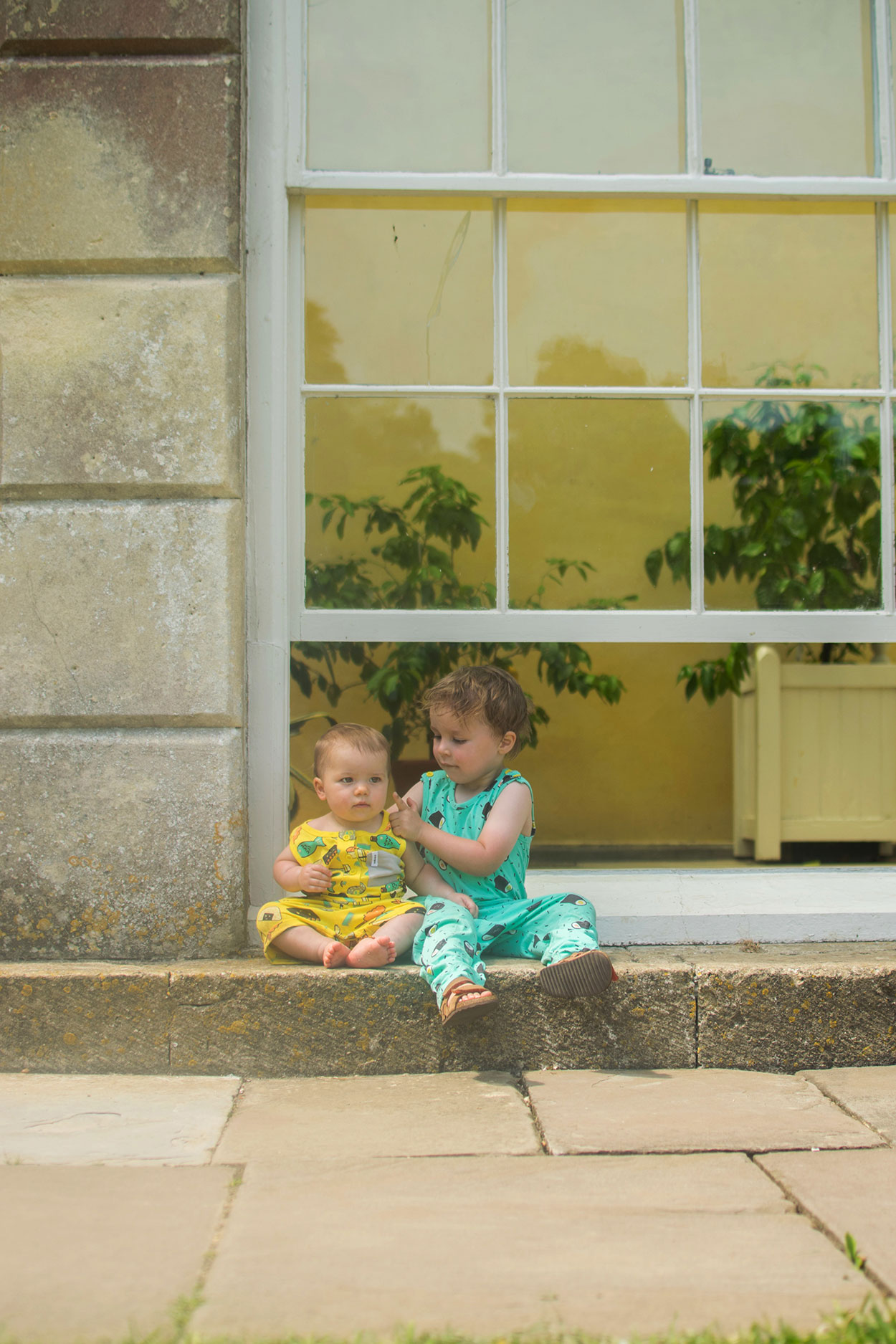 Two brothers wearing Indikidual sushi playsuits sitting together on large window of the orangery/greenhouse at Dyrham Park in Bath
