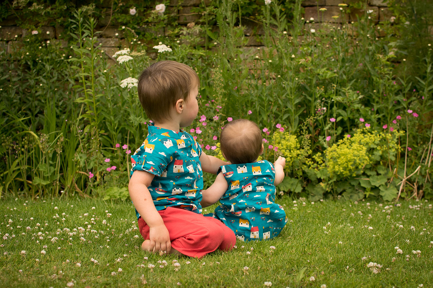 Two brothers, pre-schooler and baby wearing Sail Away playsuit and Sail Away Playaway top with Pillar Box red shorts by Little Green Radicals at Chastleton House, National Trust, near Stow0on-the-Wold - Fashion, outfits, style and bright clothes