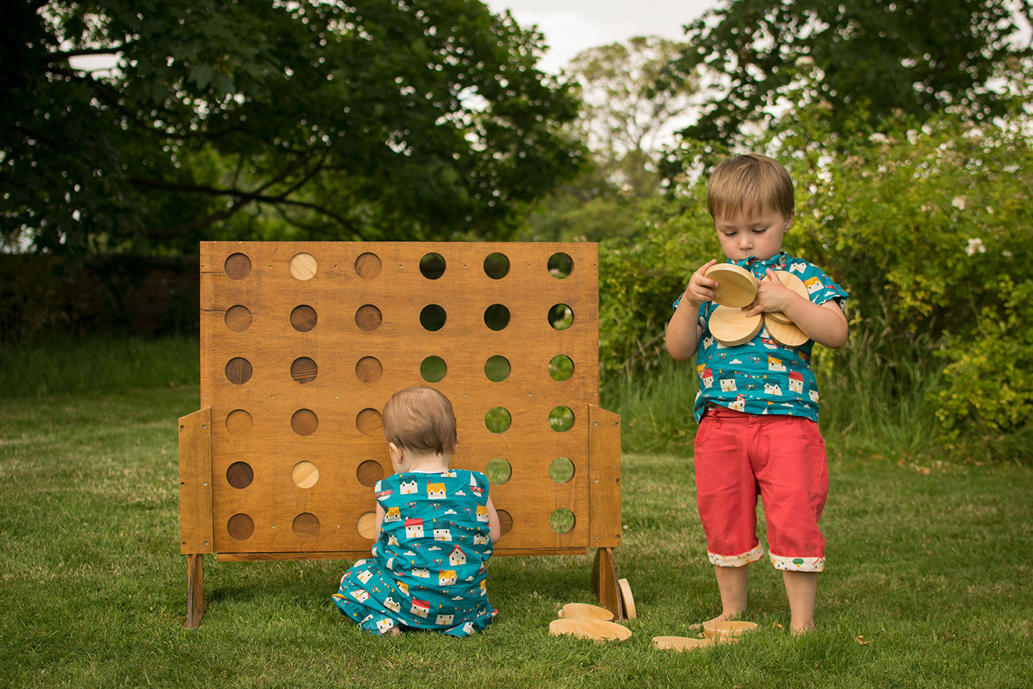 Two brothers, pre-schooler and baby wearing Sail Away playsuit and Sail Away Playaway top with Pillar Box red shorts by Little Green Radicals at Chastleton House, National Trust, near Stow0on-the-Wold - Playing with large garden wooden Connect 4 set