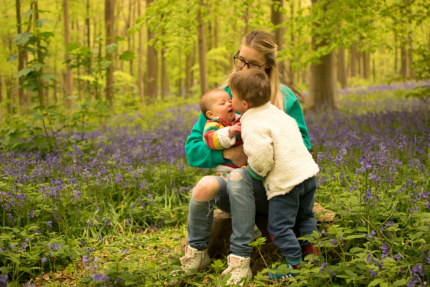 The BiBs and Us - Mother and two sons walking outside among the bluebells wearing Urban Outfitters 'K' sweatshirt and Frugi rainbow snuggle fleece with Little Green Radicals house sleepsuit