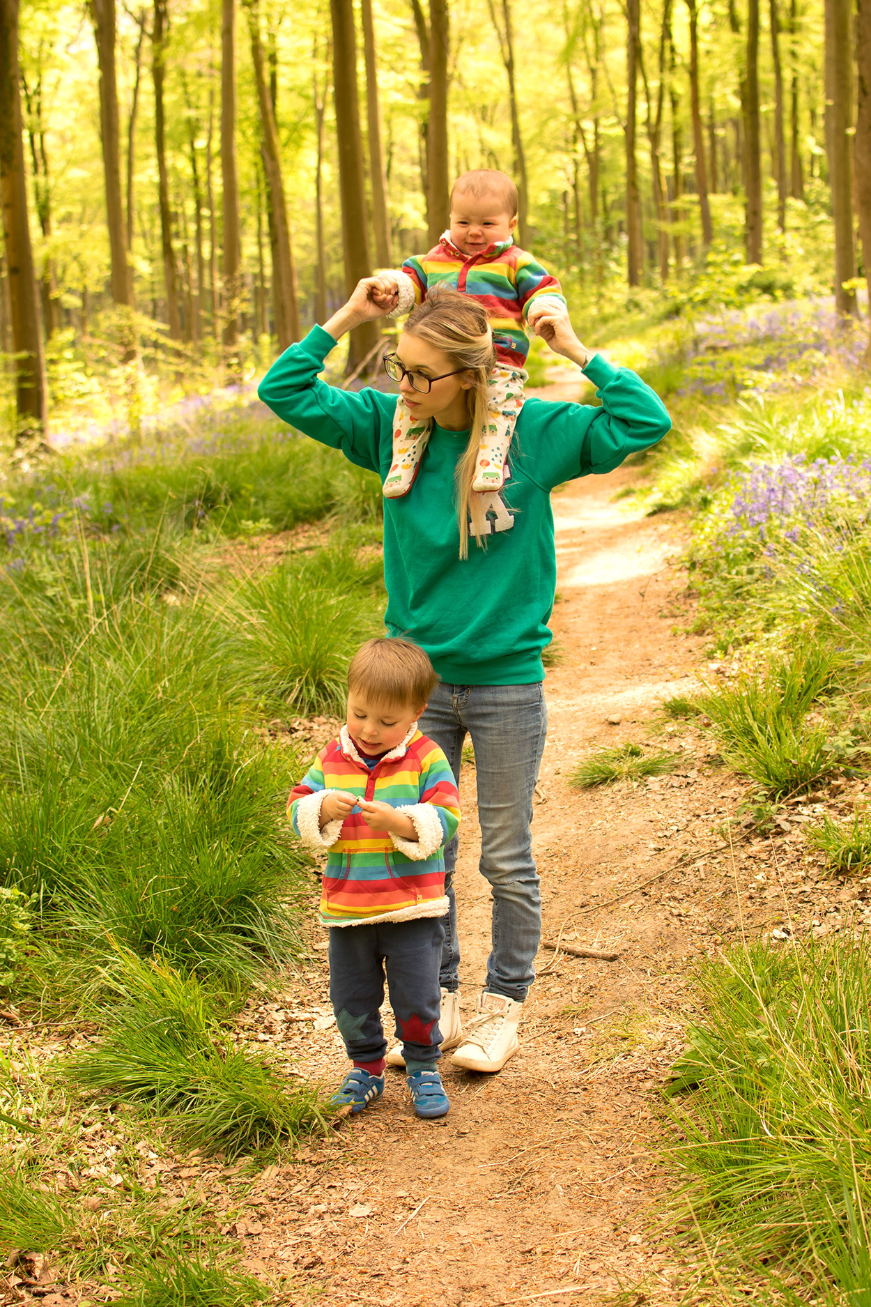 The BiBs and Us - Mother and baby son cuddling outside among the bluebells wearing Urban Outfitters 'K' sweatshirt and Frugi rainbow snuggle fleece with Little Green Radicals house sleepsuit