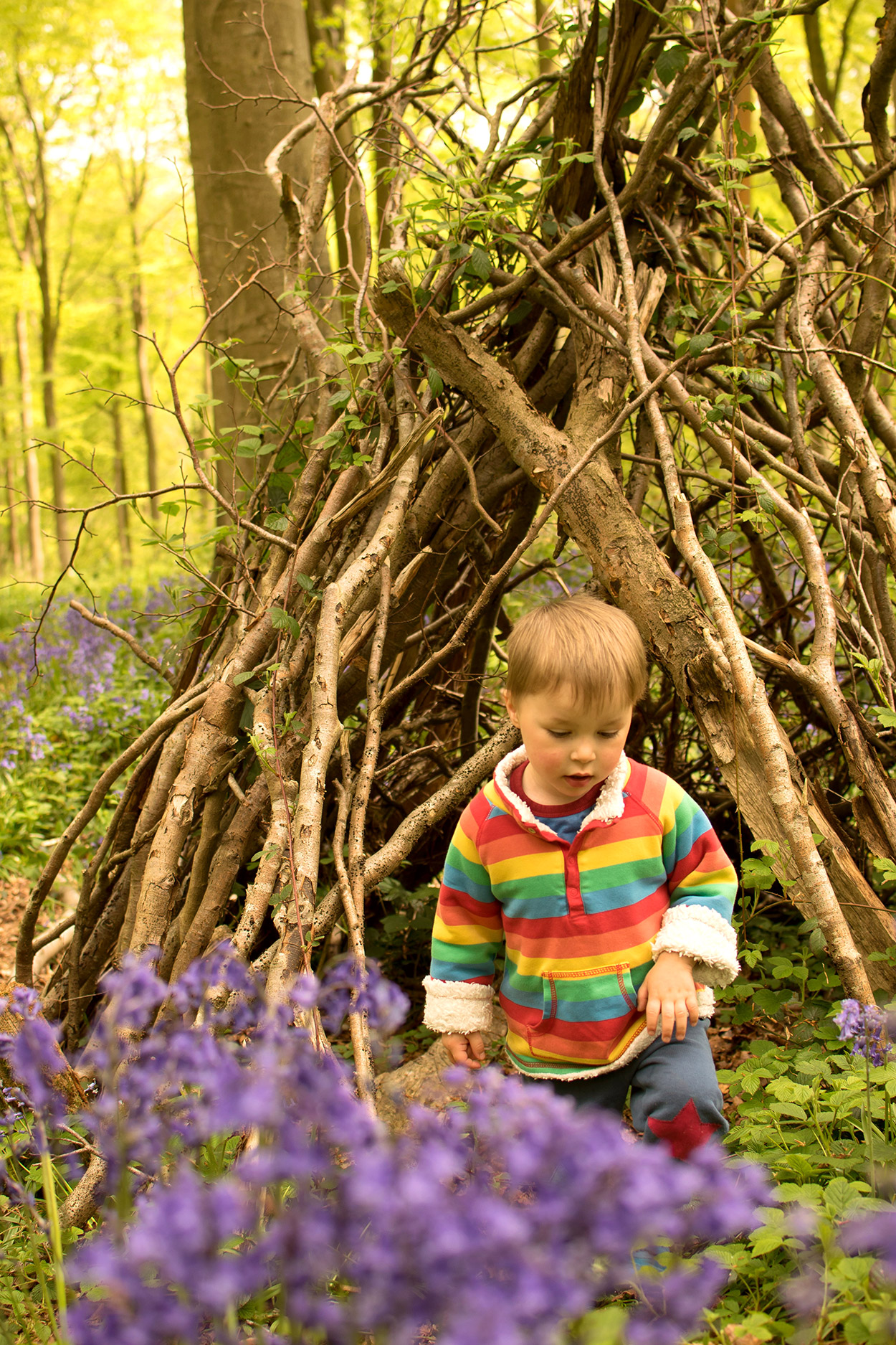 The BiBs and Us - Father and baby son cuddling outside among the bluebells wearing Urban Outfitters 'K' sweatshirt and Frugi rainbow snuggle fleece with Little Green Radicals house sleepsuit