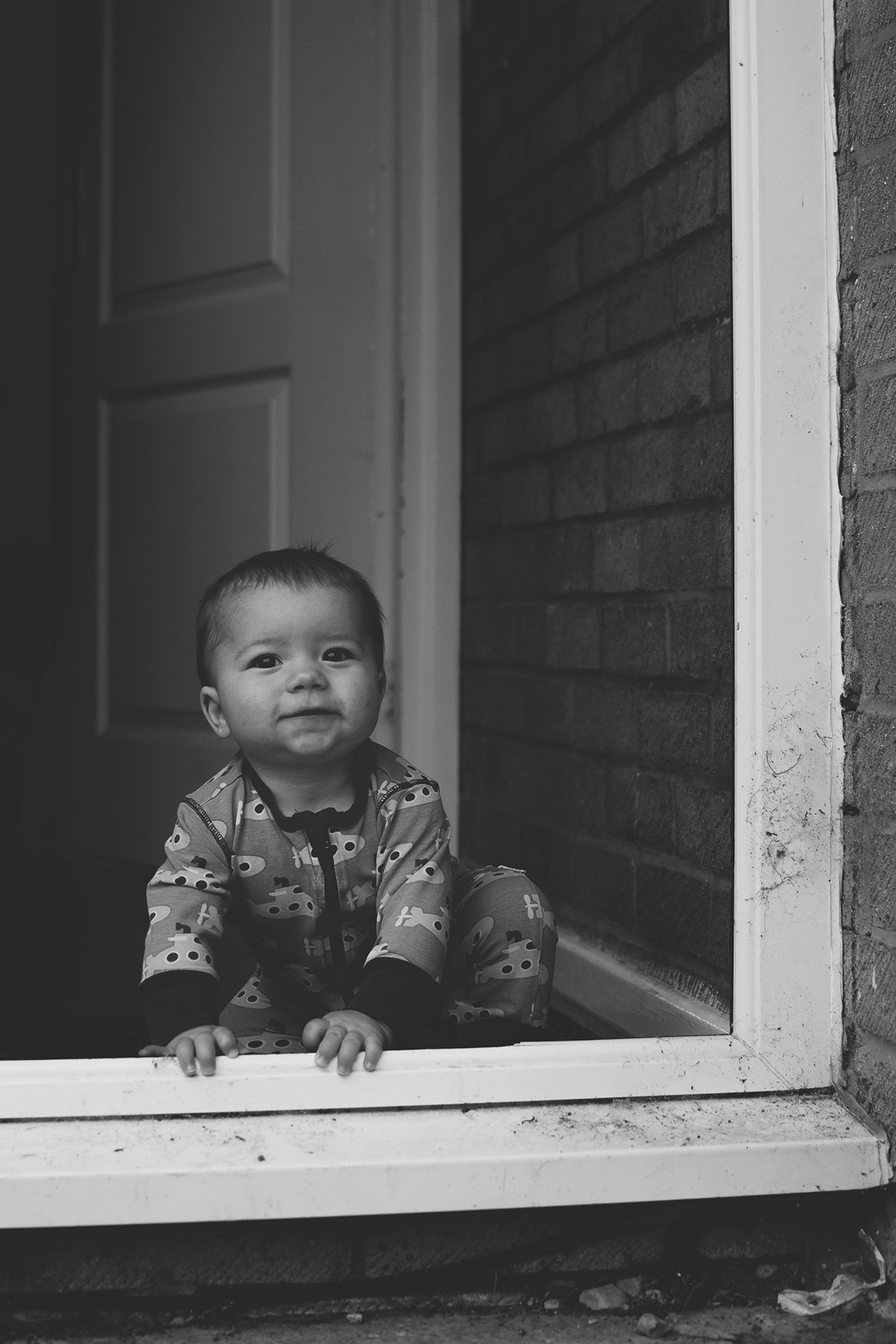 Baby Jesse Blue at 10 months old - Baby boy wearing Maxomorra submarine blue and yellow footless zip romper looking out of the door at Mum