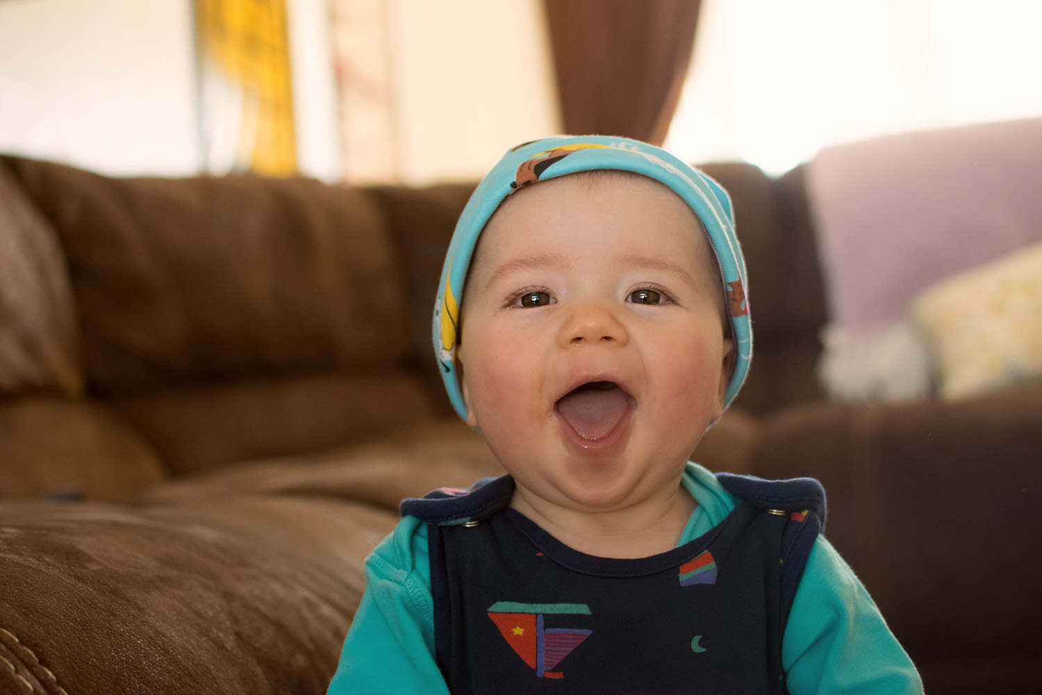 Baby Jesse Blue at 10 months old - Baby boy wearing Joules doggy print hat and Piccalilly lighthouse romper smiling and laughing at the camera whilst standing