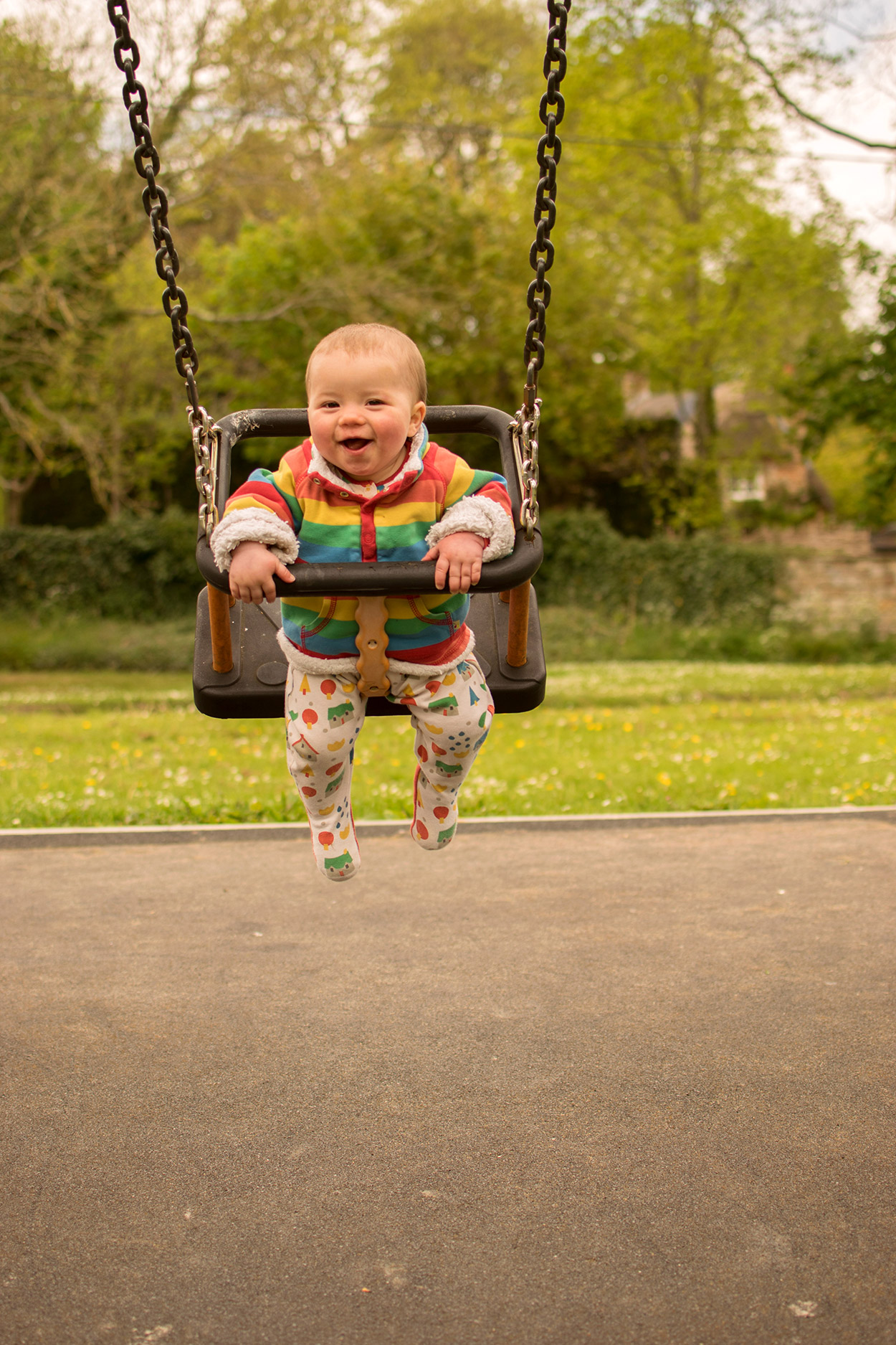 Baby Jesse Blue at 9 months old - Baby boy wearing rainbow frugi snuggle fleece and Little Green Radicals houses sleepsuit smiling whilst on the swings at the park