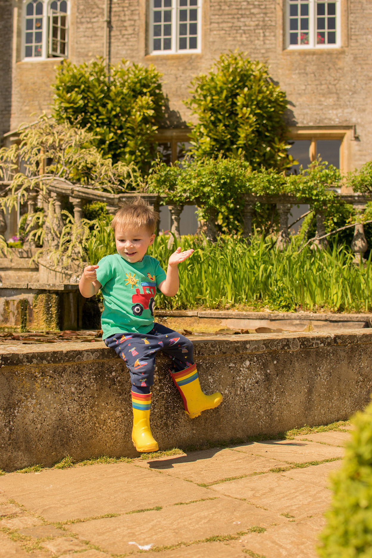 3 year old boy sitting on the wall of the pond outside the manor house wearing Frugi tractor t-shirt and Little Bird wellies at Cotswold Wildlife Park with family