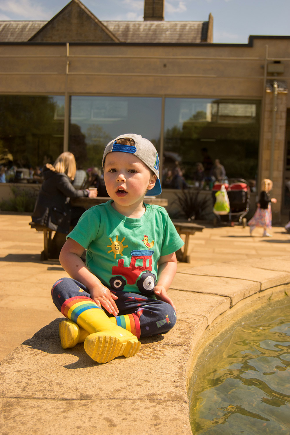3 year old pre-schooler sitting on the fountain wearing Frugi tractor t-shirt and Little Bird rainbow wellies at Cotswold Wildlife Park with family