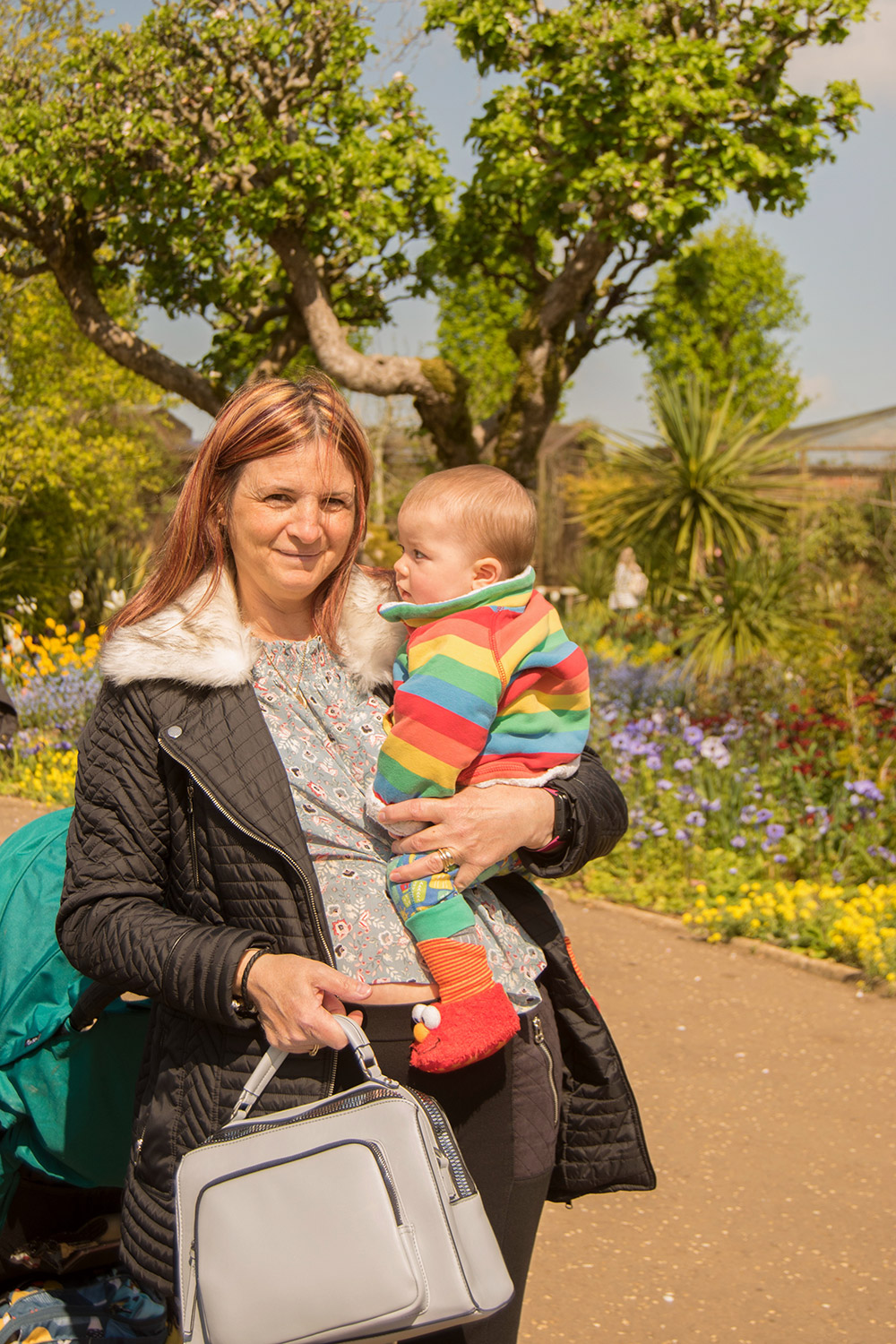 Nanny holding 9 month old baby boy wearing Frugi rainbow snuggle fleece in secret garden at Cotswold Wildlife Park with family