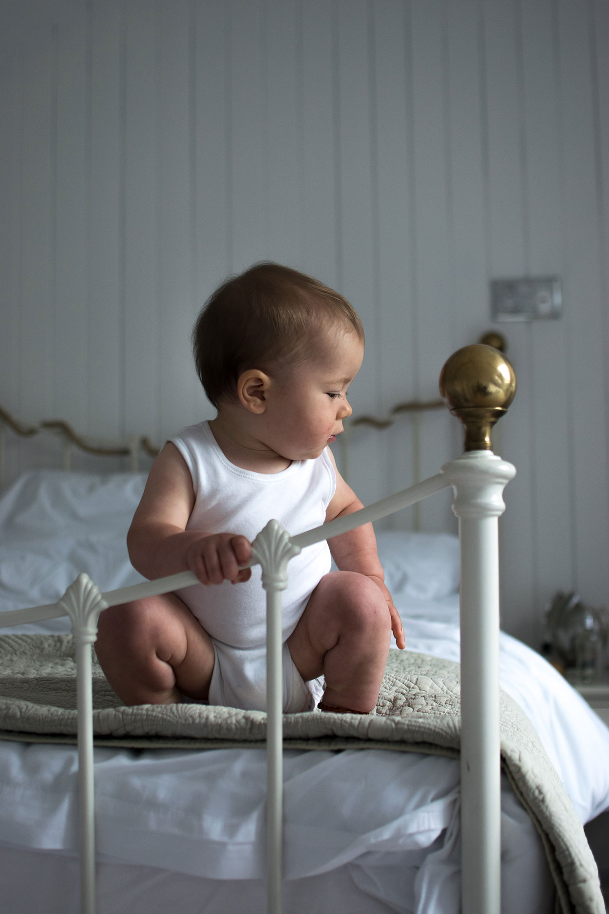 Baby boy wearing a white vest smiling and sitting on beautiful white bed in Dove Cottage in Mousehole, Aspects Holidays