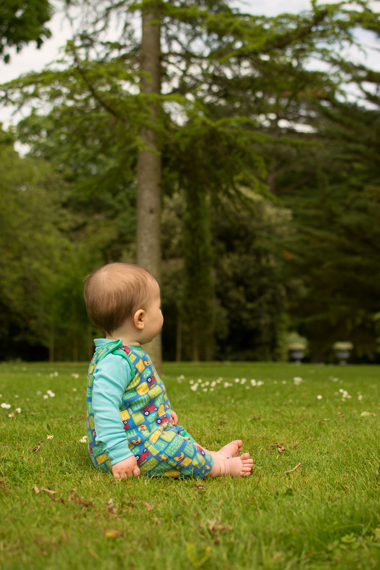 'Time to make a big decision' {The Ordinary Moments 21} - Baby boy wearing Frugi tractor dungarees sitting on the grass looking into the distance at Buscot Park, Oxford