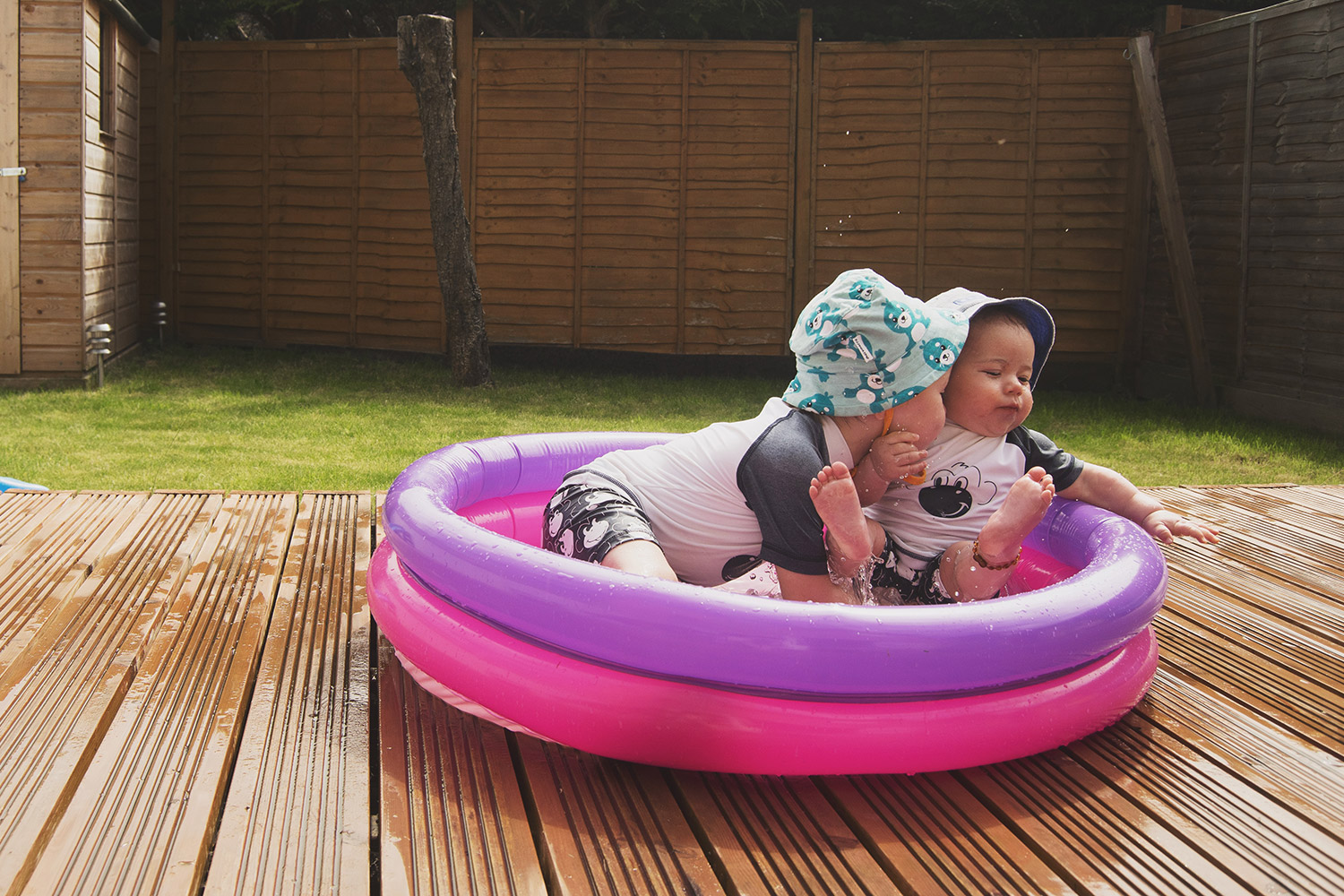 'Summer sunshine, and a new vlogging journey ahead' {The Ordinary Moments 21} - 3 year old and baby brother wearing Next matching monkey swimwear and Maxomorra seal sun hats splashing in ASDA paddling pool on a Summery day in the warm weather