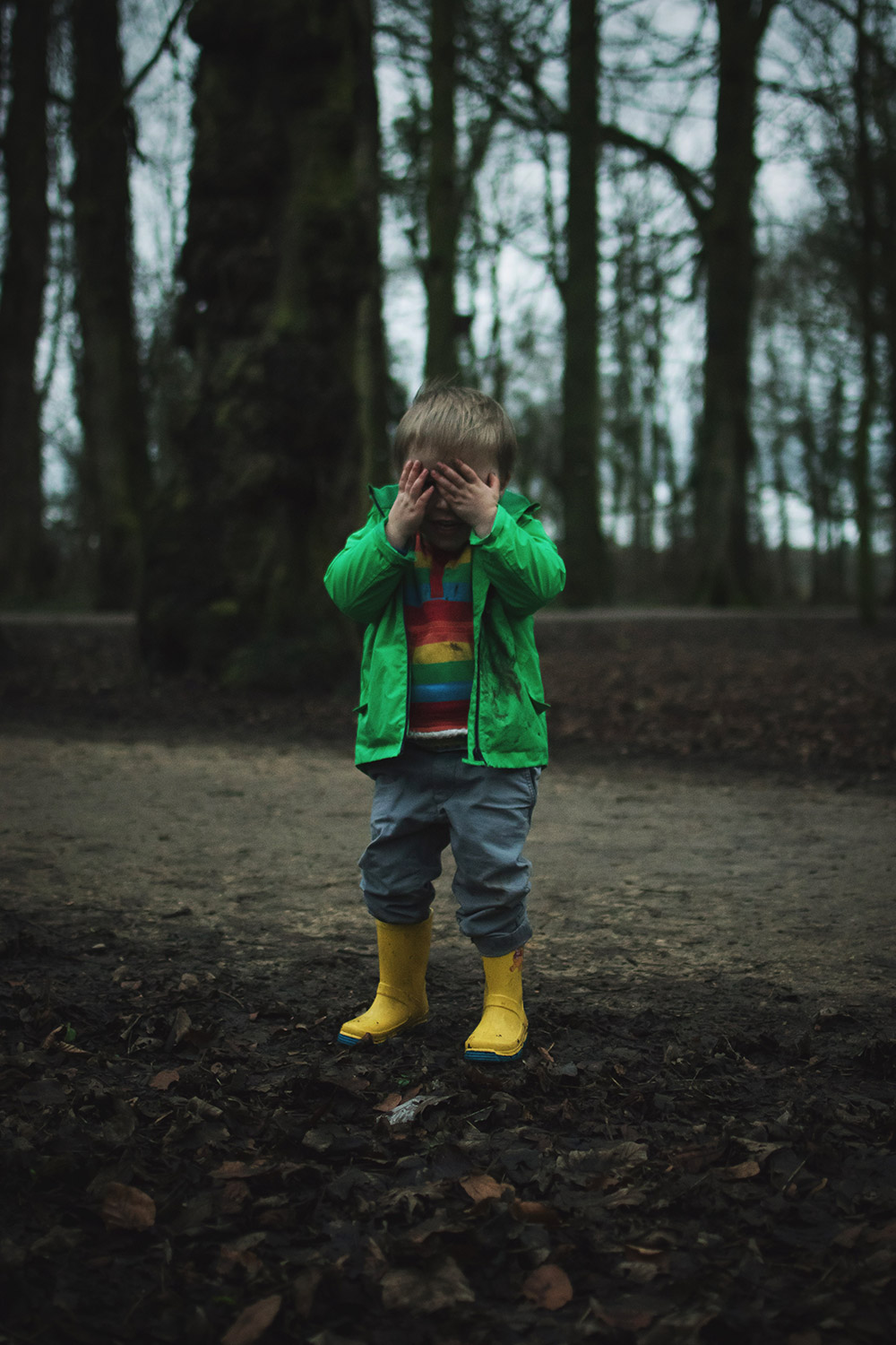 Snowdrops & Rainbows — The Ordinary Moments #17; Three year old boy wearing Frugi rainbow fleece and Next green raincoat and wellies playing in a muddy park looking for snowdrops for Spring