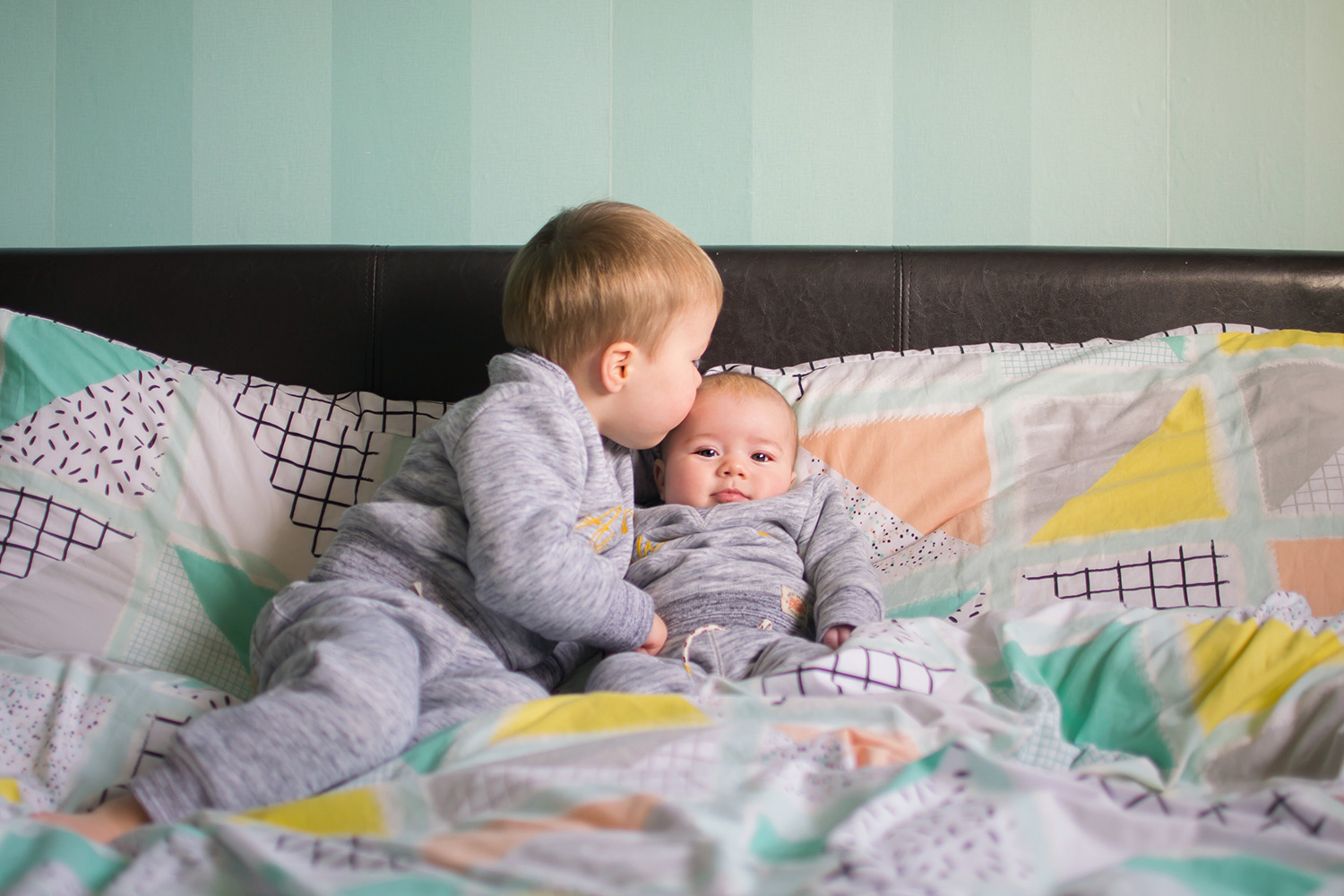 The Siblings Project {January 2017} - 4 month old baby boy and his two year old brother smiling, laughing and holding hands together wearing Mothercare Christmas cracker sleepsuit and racecar Gap pyjamas in the siblings project