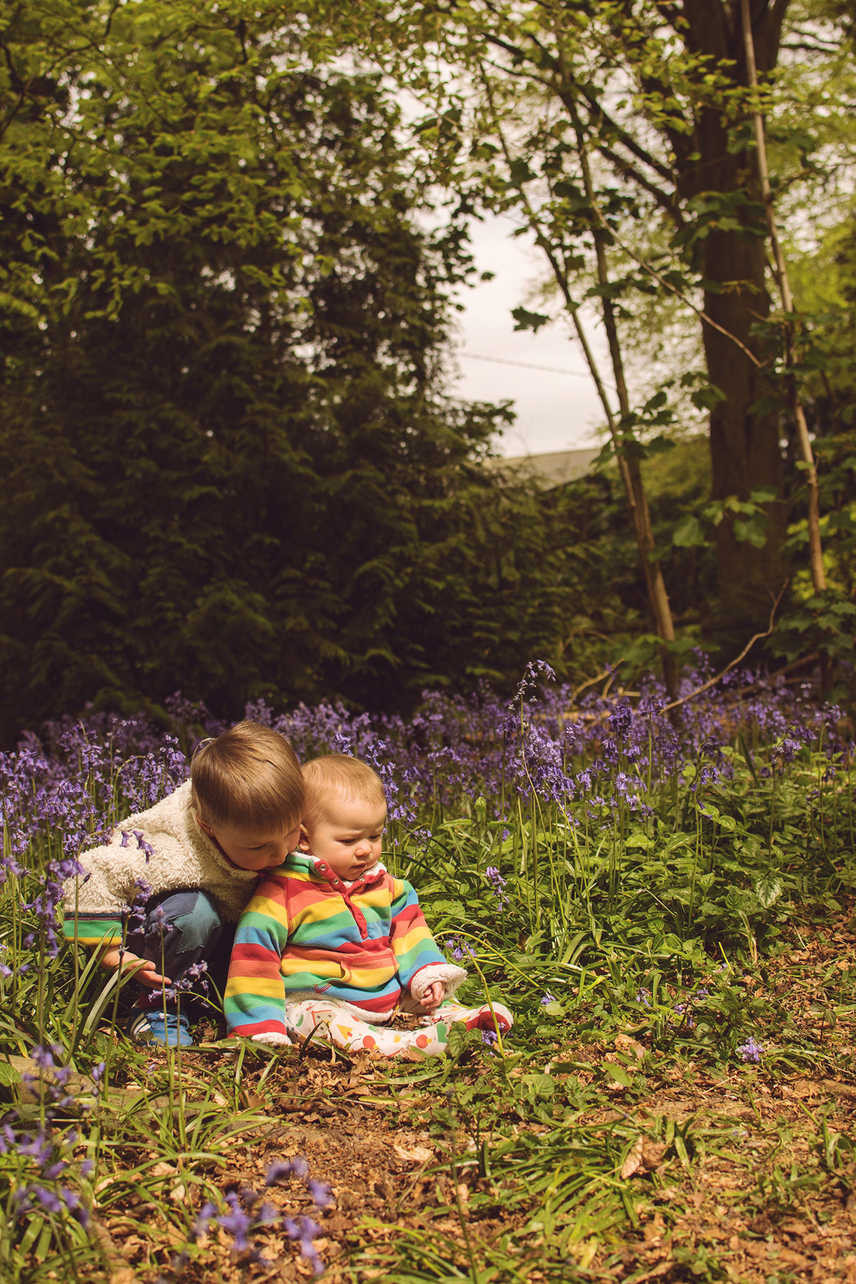 The Siblings Project {May 2017} - 3 year old pre-schooler and 9 month old baby brother wearing Frugi rainbow snuggle fleeces in bluebells of West Woods, Wiltshire, for The Siblings Project with Dear Beautiful