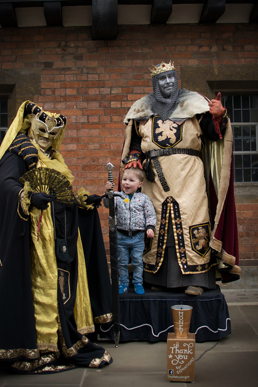 3 year old preschooler taking picture with the Shakespeare street actors in Stratford-upon-Avon on a day out with family