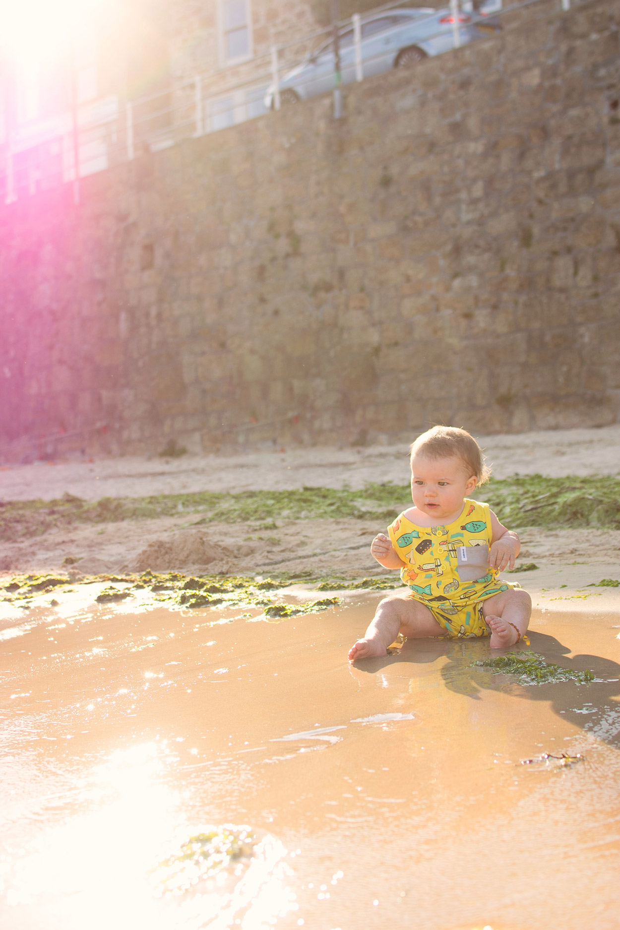 The Sand Between Your Toes {To Adventure #2} - 11 month old baby boy wearing Sushi Indikidual playsuit from Alex and Alexa sitting on the beach, playing in the sand and sea at Mousehole Harbour near Penzance in West Cornwall